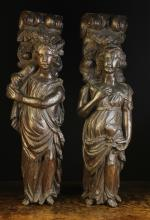 A Pair of 17th Century Carved Oak Figural Supports in the the form of ladies dressed in flowing robes; one holding a goblet, the other a cornucopia.  The scrolled capitals festooned in garlands of flowers, 32¾ ins (83 cms) high, 7 ins (18 cms) wide.*