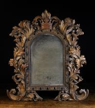 An Arched Mirror in a lavishly carved surround of crested acanthus leaves surmounted by a crown, 31 ins x 28 ins (79 cm x 71 cms).+