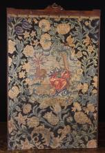 An Early 18th Century Needlework Panel depicting a lady and elephant worked in petit point to a central cartouche surrounded by gros-point scrolling foliage, 26 ins x 16 ins (66 cms x 41 cms).  And a Crewel-work panel stitched in coloured wools on a golden cream ground edged in green tassels, and depicting a huntsman with rifle, stag and lions amongst oversized flowering plants, 19 ins x 48 ins (48 cm x 122 cms). Also a small collection of woolwork panel fragments and a short length of green tasseled fringing.+