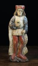 A 16th Century German Polychromed Secular Relief Carving of a Man depicted with shoulder length curly hair wearing a red cap, long white cloak and blue sleeved tunic with short gathered skirt over red hose, 18 in (46 cm) in height.