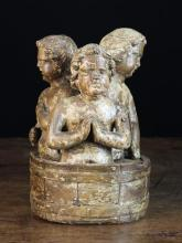A 17th Century Carved Oak Group of Three Boys (resurrected by Saint Nicholas) depicted in a barrel of brine, with traces of residual polychrome. The boys and coopered barrel carved separately, 11 in (28 cm) overall in hight.
