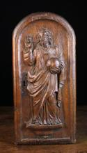 An Oak Arch-topped Tabernacle Door Circa 1700, carved in relief with a depiction of Christ; one hand raised in blessing, the other holding an orb, 19 in x 9 ins (48 cm x 23 cm).