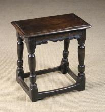 A 17th Century Oak Joint Stool. The rectangular top with moulded edge above serpentine cut rails and ball knopped rising baluster legs united by peripheral stretchers, 19½ in (50 cm) high, 19 in x 10½ in (48 cm x 27 cm).