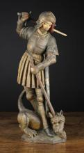 An Antique Polychromed Carving of Saint Michael & The Dragon in the 15th Century Style. Michael depicted wielding a sword and spear piercing the dragon at his feet, 16½ in (42 cm) in height.