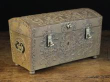 A Decorative German Patinated Steel Jewellery Casket ornamented with elaborately pierced and engraved straps and having two hasps to the front and swing handles either side. The interior lined in padded blue satin, 7½ in (19 cm) high, 12¼ in (31 cm) wide, 6½ in (16.5 cm) deep.