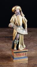 A Polychromed Oak Carving of a Prophet, Circa 1515. wearing a gilded turban and robe, holding a scroll. Mounted on a later plinth 9½ in (25 cm) in height.