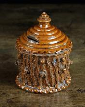 A Late 19th Century Halifax Money Box; the cylindrical bark-ware container with stepped conical top pierced with coin slot and surmounted by a finial, 6 in (15 cm) in height.