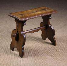A 16th Century Boarded Oak Trestle Stool. The rectangular top pierced with a central hand hold and rectangular tenons of the splayed shaped plank supports, united by a shaped centre stretcher with wedged through tenons. 18½ in (47 cm) high, 21½ in x 11 in (55 cm x 28 cm).