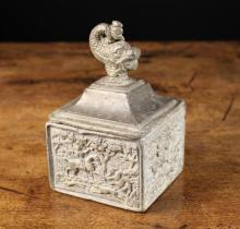 An Early 19th Century Lead Tobacco Box of square form, the lid swept up to the centre and surmounted by a dolphin finial. The sides cast with hunting scenes, 6½ in (16.5 cm) high.*