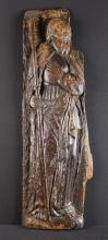 A 15th Century Oak Panel relief carved with Saint James the Lesser depicted in a long tunic tied at the waist, holding a staff. Partial loss to one side, 34½ in x 11 in (88 cm x 28 cm).