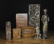 A Small Group of Wooden Panels and Carvings. A 17th century oak nulled panel enriched with punchwork, 6 in x 12 in (15 cm x 30 cm). Two 17th century Flemish oak appliqués carved in the form of angel heads; one 5 in x 4 in (13 cm x 10 cm), the other 8½ in x 2½ in (21.5 cm x 6.5 cm). A 19th century panel carved with 'The Lion of Lucerne' 5½ in x 7½ in (14 cm x 19 cms). A thick 15th century oak panel carved with Gothic tracery 6 in x 16½ in (15 cm x 42 cm). An oak carving of a monk  14½ in (36 cm) high,  a carving of a Tibetan beast 6½ in (16.5 cm) high, and a carved hardwood netsuke in the form of a mouse, 1½ in (4 cm) in length.*
