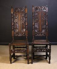 A Pair of Late 17th Century Oak Back Stools, Circa 1690. The tall pierced and carved slatted backs flanked by turned uprights surmounted by finials. The recessed panel seats on turned legs with decorative carved rails uniting the front legs, and turned H-form under-stretchers.