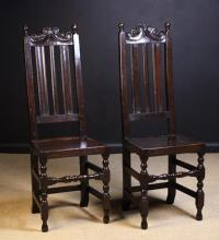 A Pair of Fine Late 17th Century Joined Oak Back Stools, Circa 1690, of good colour & patination. The tall slatted backs surmounted by pierced cresting rails carved with C-scrolls and tulip heads flanked by turned finials. The plank seats on turned legs united by twin-baluster turned front stretchers and plain side and rear stretchers, 47½ in (121 cm) high, 17 in (43 cm) wide.