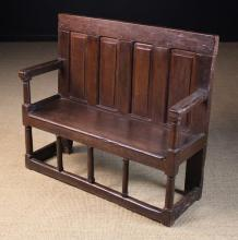 A Late 16th Century Panelled Oak Child's Settle with four fileded panels to the back and long seat above a row of column turned spindles leading down to a base rail. 32¾ ins (83 cms) high, 38 ins (96.5 cms) wide.