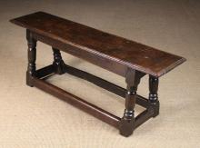 A 17th Century Joined Oak Long Stool or Bench. The plank top with moulded edge above incised zigzagged rails, standing on turned legs united by peripheral stretchers, 19 in (48 cm) high, 51½ in (131 cm) long, 12½ in (32 cm) wide.