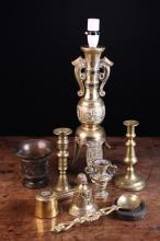 A Collection of Metalwares: A Chinese Brass Archaic style table lamp, two 19th century brass candlesticks, a small 19th century brass table bell, a small cast brass campana urn, a brass ladle, two weights and a copper warming pan with turned wooden handle.*