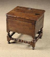 A Late 17th/Early 18th Century Joined Yew-wood Close Stool. The hinged three-plank lid with large knot loss and moulded edge, rising to reveal a void enclosed by box sides standing on turned legs united by ball, fillet and twinned baluster turned front and side stretchers with a plain stretcher to the rear, 19 in (48 cm) high, 19½ in (50 cm) wide, 16½ in (42 cm) deep.