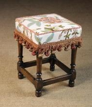 A Small Late 19th Century Upholstered Stool.  The square padded seat covered in 'crewelwork' chain-stitched with bold flowers and foliage in coloured wools on a linen ground, piped with cord and edged in tasselled fringing. The turned legs united by peripheral stretchers. 18½ in (47 cm) high, 14 in (36 cm) square.