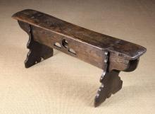 An Elm Bench. The plank seat pierced through by the square tenons of  the shaped plank end supports, connected by decorative pierced frieze boards, standing 19 in (28 cm) high, 52 in (1232 cm) long, 9½ in (24 cm) deep.
