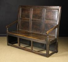 An 18th Century Panelled Oak Settle (A/F). The back composed of nine panels set in rows of three within a run moulded frame. The arms on turned posts leading to a planked seat  supported by the panelled back, panelled side (one panel missing) and square block front legs united by a low stretcher with two uprights in-between, 47½ in (121 cm) high, 59½ in (151 cm) wide, 22 in (56 cm) deep.