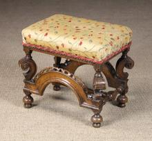 A William & Mary Carved Walnut Stool. The padded rectangular seat now covered in a golden cream silk fabric embroidered with meandering stems of flowers and foliage edge with crimson cord. The legs carved with bold crested scrolls below reel turned capitals connected by a turned H-from stretcher and moulded arched rails adorned with pierced edging to the front and rear. *