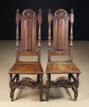 A Pair of Early 18th Century Oak Backstools, Circa 1700. The tall arch-topped fielded panel backs surmounted by moulded cresting rails pierced and carved with decorative foliage and having  voluted ends flanked by turned uprights with urn finials. The plank seats in moulded frames raised on turned legs with an arch-topped decorative rail echoing the cresting rail adjoining the front legs, and  plain stretchers to the sides and rear.