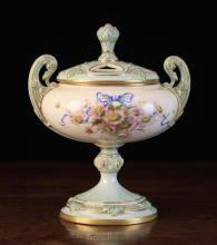 A Royal Worcester Pot Pourri Urn, hand painted with a posy of daisies tied in blue ribbon and having a decoratively moulded pale blue lid and pedestal foot enhanced with line gilding. The base with Kerr & Binns device for 1903, Rd. No. 427440, model No. 2316, 7¼ in (18.5 cm) high.