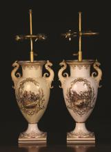 A Pair of Berlin Porcelain Lamp Vases. The cream glazed baluster bodies having griffin-headed foliate scroll handles and scenic cartouches either side depicting 18th century battle scenes framed by gilt embellishments. The tops fitted with twin light electric appliances. 23 ins (58 cms) overall height (restored).