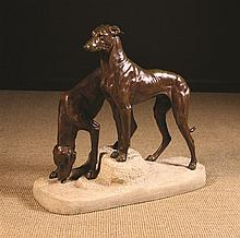 Jules Edmond Masson (1871-1932). A Pair of Patinated Bronze Grey Hounds, individually cast and mounted on a carved sandstone base with plaque inset to back inscribed 'J.E. Masson, Medaille d'Or, Salon des Artistes Français', 21½ ins (54.5 cms) in height, 22½ ins (57 cms) long, 8 ins (20 cms) wide.