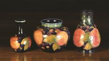 Three Pieces of 1920's Moorcroft decorated with pomegranate design on a dark blue ground: A bulbous vase 3½ ins (9 cms) high, a baluster vase 4¾ ins (12 cms) high, and a small gourd vase 3½ ins (9 cms) high.