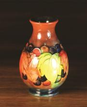 A Small Moorcroft flambé glazed Vase decorated with leaf and fruit design, Circa 1920's, 4½ ins (11 cms) in height.