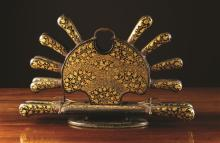 A 19th Century Indo-Persian Lacquered Cutlery Stand, decorated with intricate scrolling gilt flowers. The flat rounded holder with a handle to the top flanked by a fanned arrangement of eight knives and twin pronged forks, above pairs of carving knives and forks, 11½ ins (29 cms) high, 17½ ins (44.5 cms) in length, 2 ins (5 cms) wide.
