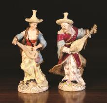 A Pair of Potschappel Porcelain Figures of Musicians strumming lutes (A/F). The figures wearing Asian style costume and standing on Rococo scrolling bases enriched with gilding. Underglaze blue marks and impressed 710F and 711F on bases. The male 7¼ ins (18.5 cms) high, the female 7½ ins (19 cms) high (A/F).