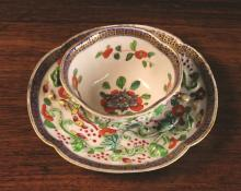An 18th Century Qianlong Period Porcelain Teabowl and Saucer of oval quatrefoil form. Both pieces embellished with moulded trails of scrolling  lotus leaves, and small gilded mice on a polychrome enamelled ground of flowers, scrolls and butterflies. The saucer 4¾ ins x 4¼ ins (12.5 cms x 11 cms), the teabowl 1¾ ins (4.5 cms) high.