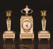 A Charming Louis XVI Style White Marble Clock Set with gilt bronze mounts intricately cast with laurel sprays,pendant garlands and beading. The clock with enamelled dial in a rectangular case surmounted by an urn finial, 7½ ins (19 cms) high. The accompanying candlesticks with urn shaped candle cups cast with stiff leaves above square tapering stems and plinth bases raised on toupée feet, 6 ins (15 cms) high.