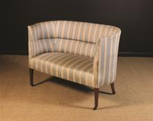 An Edwardian Upholstered Tub Settee covered in cream and blue striped fabric and standing on square mahogany legs tapering down to brass caps and castors, 34 ins (86 cms) high, 47 ins (119.5 cms) wide.