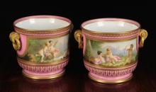A Pair of Fine 19th Century Porcelain Rose Pompadour Cache Pots, hand painted with landscapes on one side and cherubs at play on the other. The pink borders enriched with gilding, 6½ ins (16.5 cms) high, 7 ins (18 cms) in diameter.