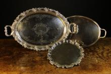 Three Silver Plated Trays: One being a salver raised on three scroll knop feet with a moulded 'Chippendale' border, stamped on underside C & R CALCUTTA, 12½ ins (32 cms) in diameter. An Elkington & Co flat oval tray with foliate sprays to the reeded twin handles, 22¼ ins x 13 nins (57 cm x 33 cs). A large oval tray with scrolling foliate engraving, a decoratively pierced band to the border and scrolling border cast with fruiting vine and incorporating scroll handles, 27 ins x 16½ ins (69 cms x 42 cms).