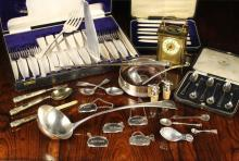 A Collection of Silver & Plated Ware, and a Brass Carriage Clock. To include a Georgian Silver Soup Ladle by Peter, Ann & William Bateman hallmarked London 1804, a silver gilt knife, fork & spoon set with Birmingham hallmarks for 1829, two silver caddy spoons, a Georgian silver teaspoon, a cased set of silver coffee spoons hallmarked Sheffield 1963 by Cooper Brothers & Sons Ltd, a cased set of pretty mother-of-pearl handled fruit knives, a Deakin & Francis Ltd silver handled button hook Birmingham 1895, a silver mounted bottle coaster Birmingham 1992, a pair of bottle stoppers with grouse finials, plated decanter labels, a plated sauce ladle, and a case of Walker & Hall fish cutlery.