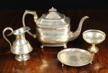 Four Pieces of Silver to include; A small 19th century Irish salver with Dublin assay marks and Joseph Jackson maker's stamp (1795..1804). A 19th century Russian silver jug stamped 1887. A small silver comport with pierced trellis border and a pedestal foot, hallmarked Birmingham 1928 with William Devenport maker's punch. A George III teapot hallmarked London 1807 with Peter & William Bateman maker's punch.