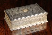 A Fine Persian Silver Cigar Box of rectangular form, extensively engraved with intricate decoration; the hinged lid centred by a gilt coronet appliqué. 2¼ ins (6 cms) high, 8¼ ins (20 cms) wide, 5 ins (13 cms) deep.