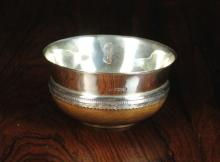 A George V Silver Mazer with turned maple base, hallmarked Sheffield 1921 with Thomas Bradbury & Sons Ltd maker's punch.