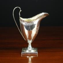 A Georgian Neo-Classical Silver Creamer hallmarked London 1792, the helmet shaped vessel engraved with foliate decoration and standing on a pedestal foot.