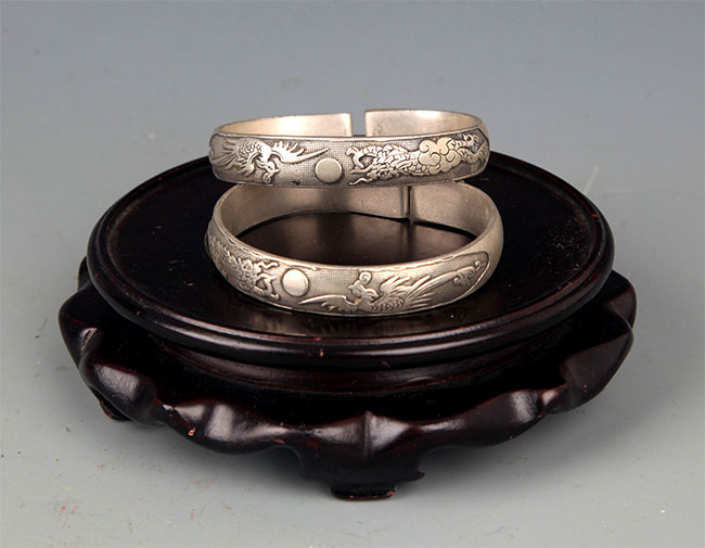 A PAIR OF FINELY CARVED SILVER PLATED BANGLE