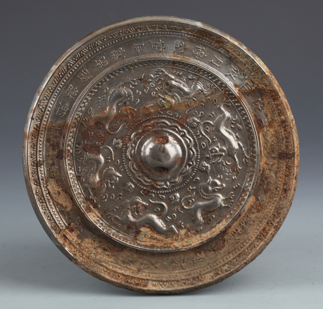 AN OLD FINELY CARVED BRONZE MIRROR