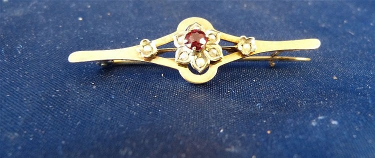 A 9ct Gold Bar Brooch set with centre garnet surrounded by half p
