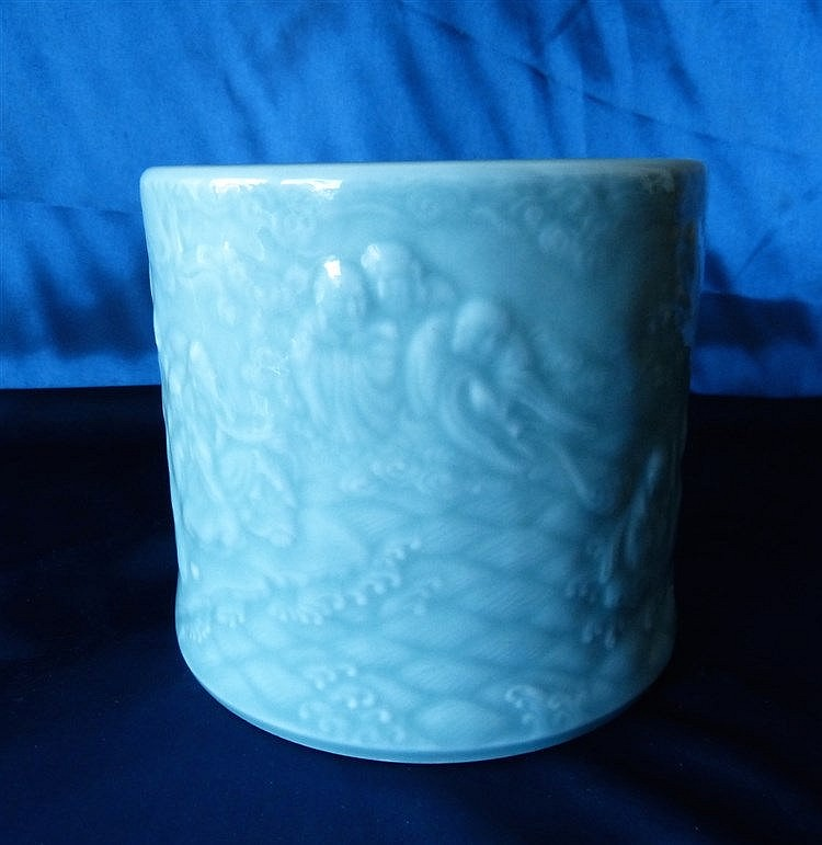 An Oriental Celadon Style Brush Pot having raised figure decorati