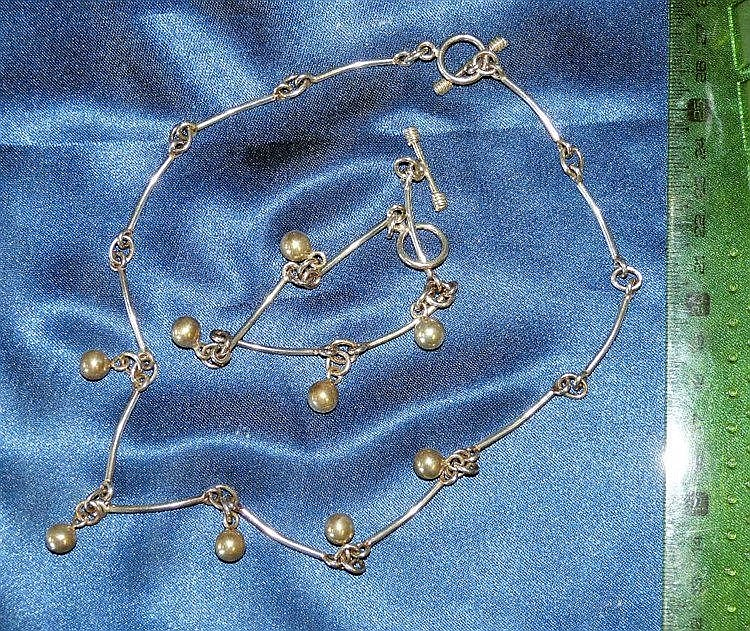 A Silver Necklace having various drops, also a matching bracelet