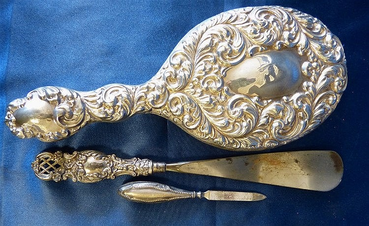 A Birmingham Silver Hand Mirror having embossed leaf and scroll d