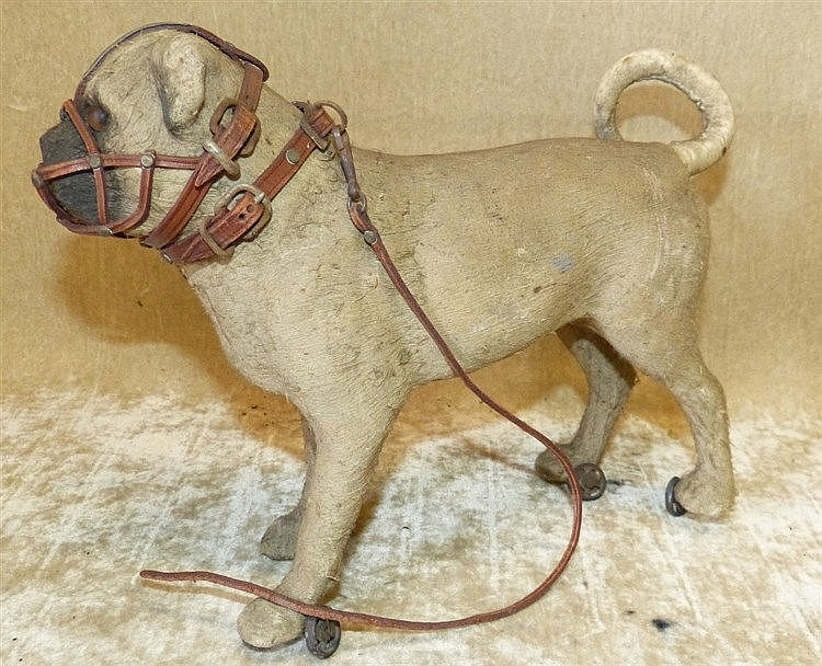 A Child's Papier Mache Model of a Dog wearing a muzzle on wheels,